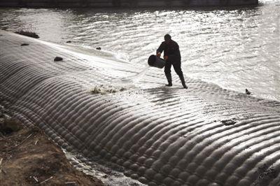济宁古运河与新运河交界处,工人正在冲洗堤坝表面。这里正在进行的是南水北调东线工程的一部分。