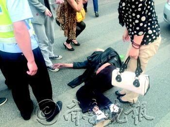 受伤老人躺在地上打哆嗦,李女士脱下外套给老人盖上。