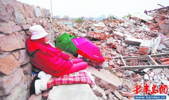 钟清先的儿媳妇初女士正在守护老房废墟。