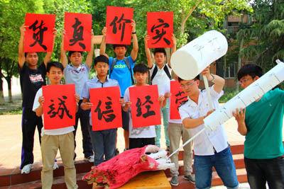 """5月16日,在山东聊城大学,大学生们手举""""货真价实 守诚信经营""""的牌子,用行为艺术宣传食品安全"""