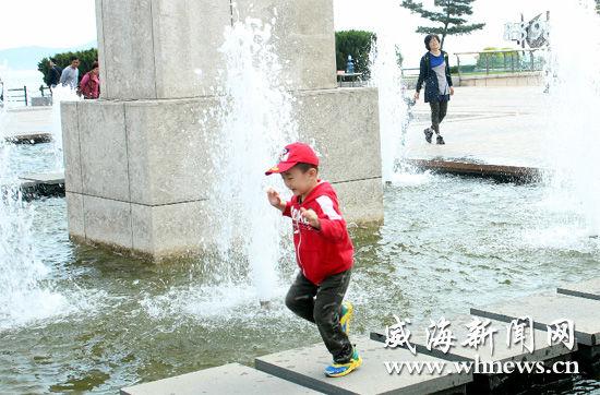 昨日上午,一名儿童从幸福门广场的水池边开心地跑过.