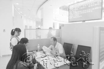 26日,在招聘会上,企业招聘人员正在与毕业生交流。 李珍梅 摄