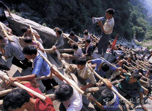 一百多名挑夫合力将巨石沿盘道抬上泰山,场面壮观