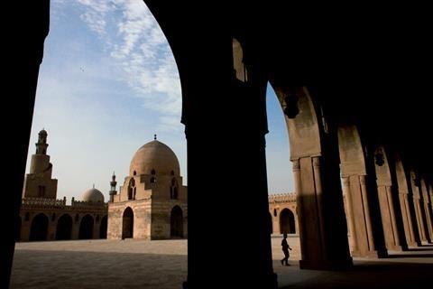 埃及人路过开罗中世纪法蒂玛王朝时期修建的古城墙。