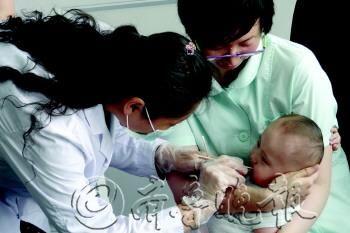 工作人员为男婴采集DNA样本。