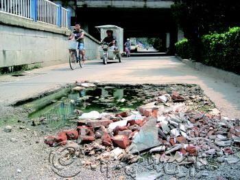 坑里很多积水、建筑垃圾,十分危险。 本报记者 吴金彪 摄