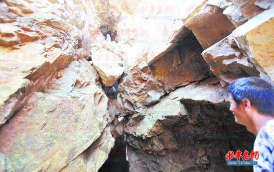 ▲矿坑周围的岩石出现裂缝随时可能坍塌。