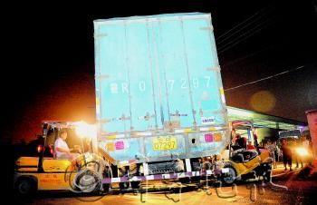 23日晚,工人用两辆小型叉车转移堵在快递公司门口的货车。  本报记者 邱志强 摄