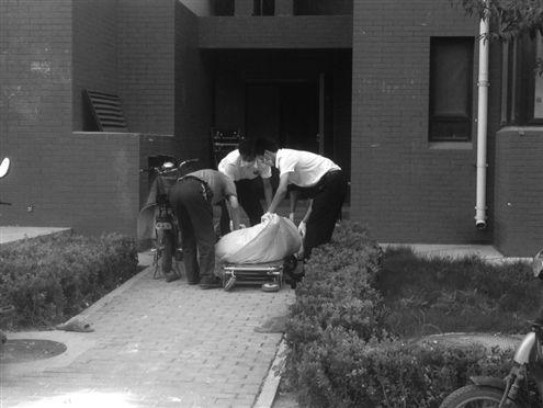 工作人员将老人遗体运走 记者郑芷南实习生张宁摄