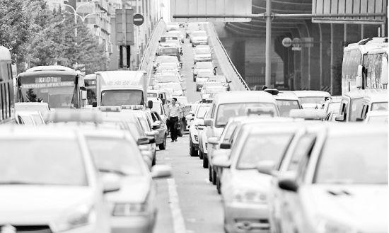 昨日上午,出城的几条道路出现拥堵。图为北园高架路中段下桥口处车辆排起长队。(王锋 摄)