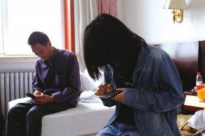 父女俩相顾无言,只能低头玩手机。京华时报记者谭青摄
