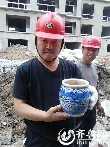 施工人员拿着从墓坑内取出的瓷瓶
