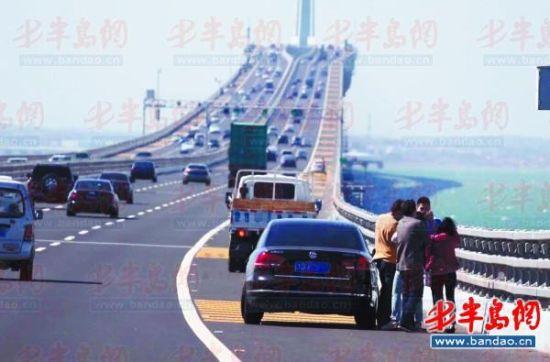 10月2日,胶州湾大桥,不少游客将车停在应急车道拍照看景。
