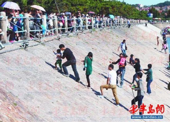 栈桥东侧堤坝上,游客利用粗绳往返海滩与岸上。记者 孟达 摄