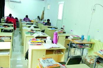 济南大学西门附近一处收费考研自习室内放了20多张桌子。