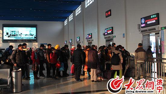 济宁汽车总站中正在排队等候检票的旅客