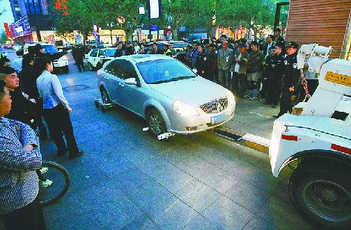 昨日傍晚,泉城路鞭指巷南段,交警劝说未果后,将违章车辆拖走。(黄中明 摄)