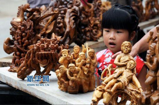7月7日,山东省临沂市郯城县马头镇宋庄村一名小女孩被抗战主题木雕吸引。新华社发(房德华 摄)