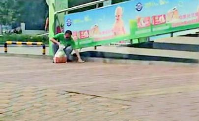 盲人捡起饮料瓶扔进路边垃圾桶