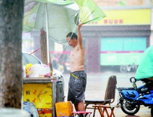 17日16时许,狂风裹挟急雨突袭泉城,在泺源大街,来不及收摊的摊主用手拽住遮阳伞,防止伞被大风吹走。 本报记者张中 摄