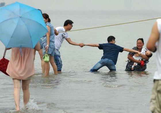7月18日,武汉,抱婴投江的女子与几位施救小伙在江水中僵持。(来源:倚天/东方IC)