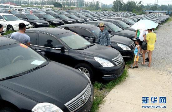 7月20日,市民在山东枣庄一家拍卖公司场地上查看待拍公车。当日,标有序号的103辆公车整齐地停放在山东枣庄一处拍卖公司场地上,许多市民冒着酷暑前来查看。山东省枣庄市党政机关的103辆公务用车将于7月23日至25日在中国拍卖行业协会网络平台的5个大厅进行公开拍卖,如此大规模的政府公车拍卖在山东属首次。自2013年底,枣庄市启动了公车清理整顿工作,251个市直部门及各级党政、人大、政协、法院、检察院等领域全面开展自查自纠行动。目前,通过公开招标方式,中标评估机构已经对部分被清理的公车进行了价格评估。据悉,枣庄启动的网上公车拍卖,收入全部上缴国库。新华社记者 冯杰 摄