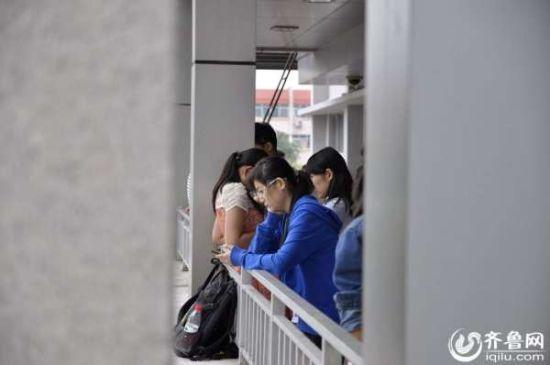 课间休息时间,学生挤在体育馆门口休息。