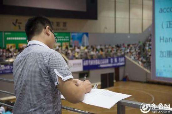 图为一名参加培训的男生站在走廊处,一边认真听讲,一边迅速做着笔记。