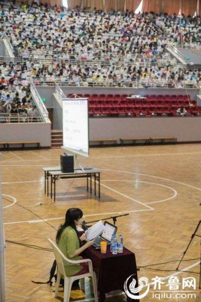 图为一名英语培训教师独自一人坐在体育场中间讲课。