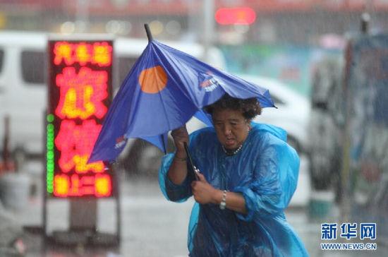 """7月25日,在烟台市西大街,出行的市民在雨中赶路。受今年第10号台风""""麦德姆""""影响,山东省气象台于25日6时继续发布暴雨橙色预警信号:威海、烟台、青岛、日照、潍坊5市仍有暴雨局部大暴雨,雨量50到100毫米局部可能超过150毫米,东营、滨州、淄博3市有中到大雨局部暴雨,雨量20到40毫米局部50到100毫米,其他地区有小到中雨局部大雨,雨量5到15毫米局部30毫米左右。新华社发(申吉忠 摄)"""