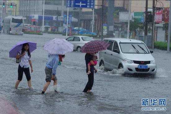 """7月25日,山东日照市民在雨中出行。受今年第10号台风""""麦德姆""""影响,山东省气象台于25日6时继续发布暴雨橙色预警信号:威海、烟台、青岛、日照、潍坊5市仍有暴雨局部大暴雨,雨量50到100毫米局部可能超过150毫米,东营、滨州、淄博3市有中到大雨局部暴雨,雨量20到40毫米局部50到100毫米,其他地区有小到中雨局部大雨,雨量5到15毫米局部30毫米左右。新华社发(张磊 摄)"""