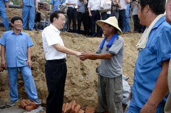 """总理与鲁文才亲切握手(图片来源于新华社""""新华视点""""微博)"""