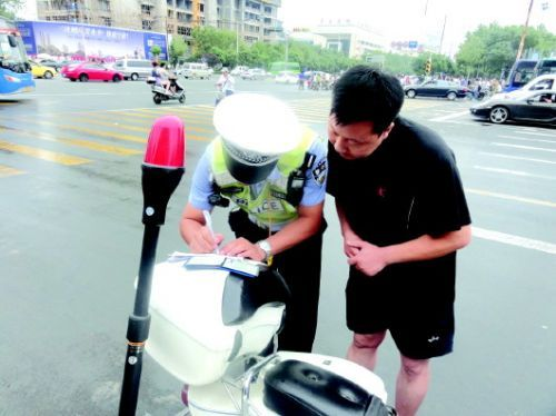 交警向不礼让行人的司机开出了罚单。