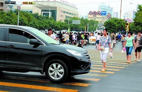 这辆车右转的时候不停车礼让行人,司机被交警现场开罚单。