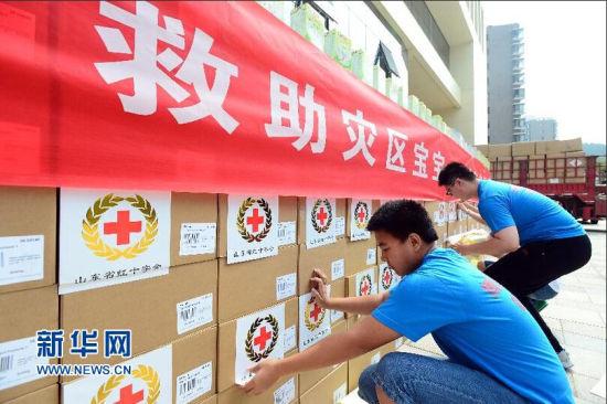 8月7日,在山东省红十字会救灾备灾中心,爱心志愿者在捐赠物资上贴上标签。新华社记者 郭绪雷摄