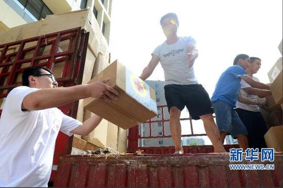 8月7日,在山东省红十字会救灾备灾中心,爱心志愿者搬运捐赠物资。新华社记者 郭绪雷摄