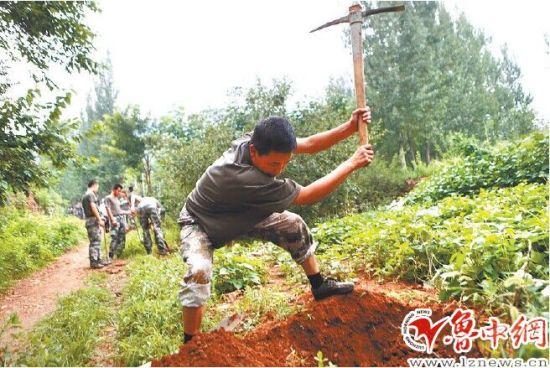 西河镇龙台村对面的山上,官兵将山路边埋藏的水管挖出,进行维修和更换。