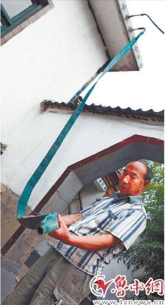 为了收集雨水,护宝泉村村民封明俊在房顶落水管的出口处,接上了收集雨水的水管。