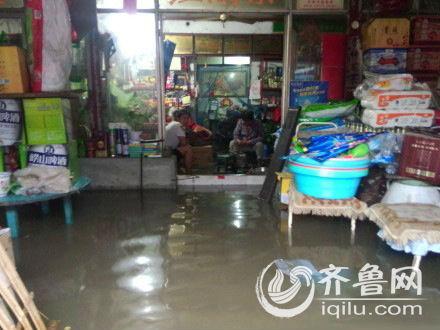 面对暴雨积水,无奈的商户们只能蜷缩在铺子里。