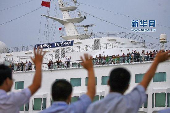 """8月16日,在山东烟台港,人们向""""中华泰山""""号邮轮上的游客挥手告别。新华社发(唐克 摄)"""