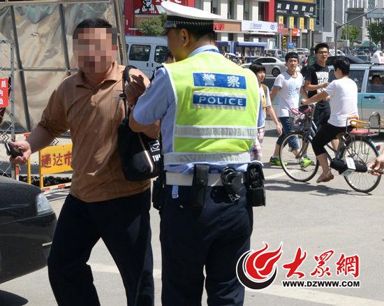 民警将一名正在闯红灯的行人制止。