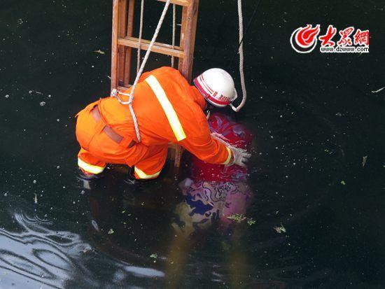 消防救援人员将绳索固定在尸体上进行打捞