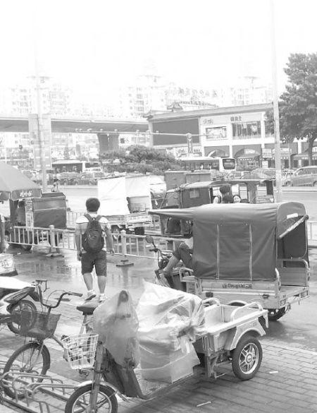 """济南火车站和长途汽车站外聚集着很多""""摩的"""",钻空揽活。本报记者 韩笑 摄"""