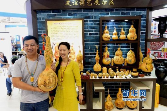 8月28日,来自山东章丘的葫芦艺术家马友谊夫妇在文博会上展示他们制作的彩刻葫芦。新华社记者冯杰摄