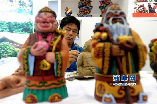 8月28日,山东烟台市非物质文化遗产项目栖霞泥塑传承人陈玉录在文博会上制作泥塑作品。新华社记者冯杰摄