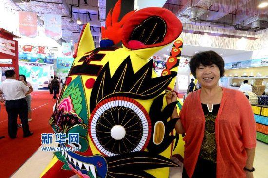 8月28日,来自山东滨州的博兴布老虎文化传承人刘清华在文博会上和她制作的大型布老虎合影。 新华社记者冯杰摄