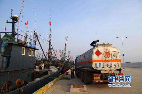 8月30日,山东日照渔民在给船只装载燃油。(张磊 摄)