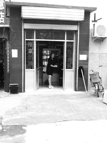 ◤12日上午,在济南黄台社区魏家村的一家刚被责令停业的诊所内,店内女子对周围的人十分警惕。见习记者王建伟摄