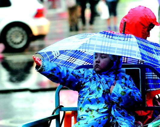 9月14日,济南市气温降到18℃,一个小孩伸手接雨感受秋意。