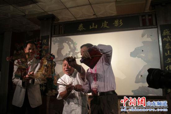 国家级非物质文化遗产泰山皮影传承人范正安正在指导皮影爱好者操作皮影人物。陈倩倩摄